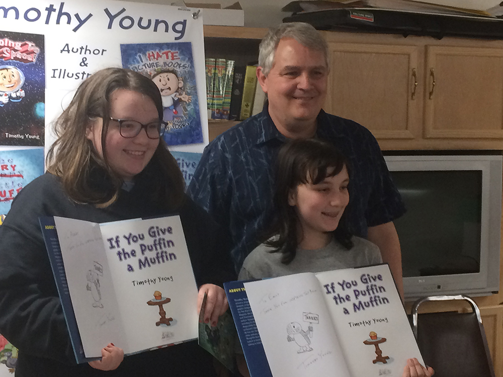 Ashley Nietupski and Emily Horvath get signed copies thanking them for being the inspiration for author/illustrator timothy Young's If You Give the Puffin a Muffin