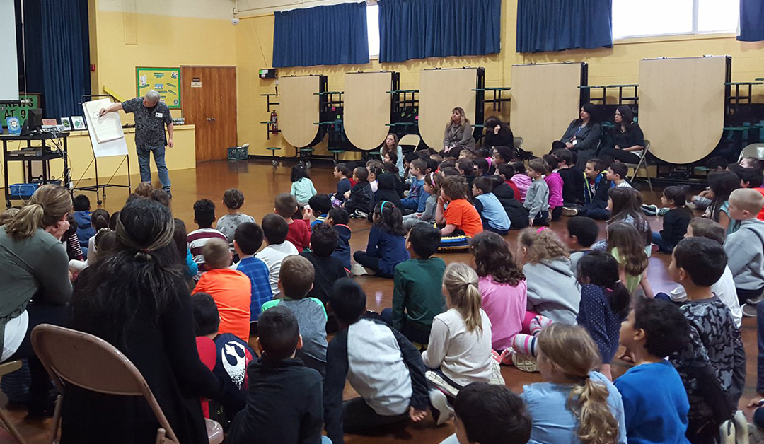 Author/illustrator Timothy Young draws his puffin character at an elementary school assembly.